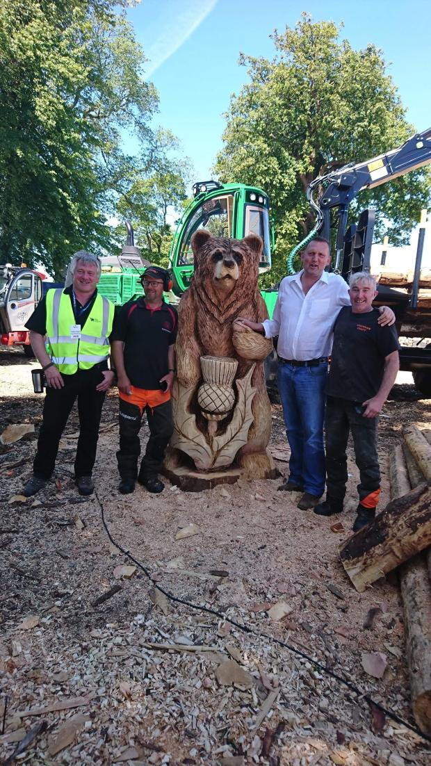Forestry Journal: At the Royal Highland Show in 2018, Iain, Pete Bowsher, and Andy Maclachlan carved a bear for Doddie Weir's MND charity auction. Pictured left to right: Graeme Hodgson (RHS), Iain, the bear, Doddie and Andy.