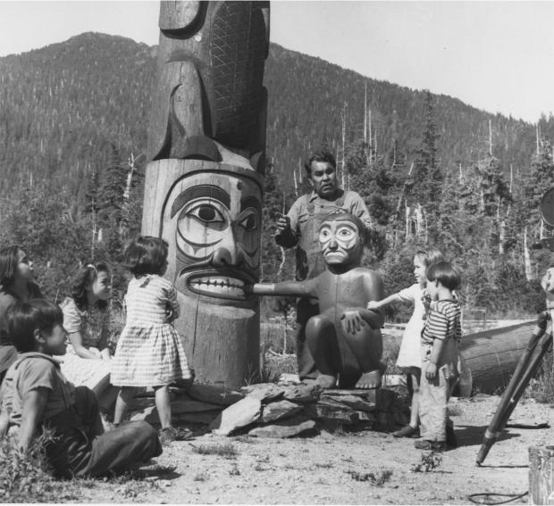 Forestry Journal: Tlingit carver Henry Denny Sr was one of the few older men enrolled in the Civilian Conservation Corps. Project leader Linn A Forrest photographed Henry with his grandchildren and the Giant Rock Oyster Pole. (Photo credit: USDA Forest Service.)